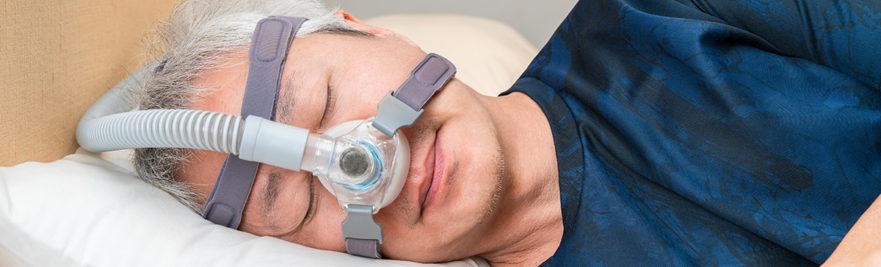 man sleeping with CPAP - sleep apnea