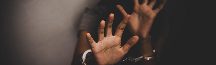 Handcuffed hands held up in defense